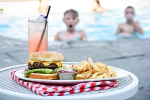 Closeup on Cheeseburger and Fries with Pink Lemonade Served at Grand Hotel of Mackinac Island While Children in Swimming Pool Look on From the Background